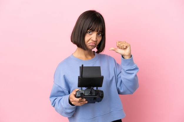 誇りと自己満足のピンクの背景に分離されたドローンのリモコンを保持している若い混血の女性
