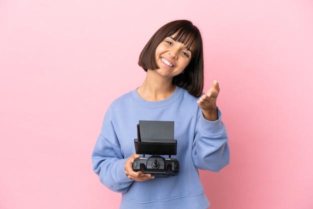 Молодая женщина смешанной расы, держащая пульт дистанционного управления дроном, изолированная на розовом фоне, пожимая руку для заключения хорошей сделки