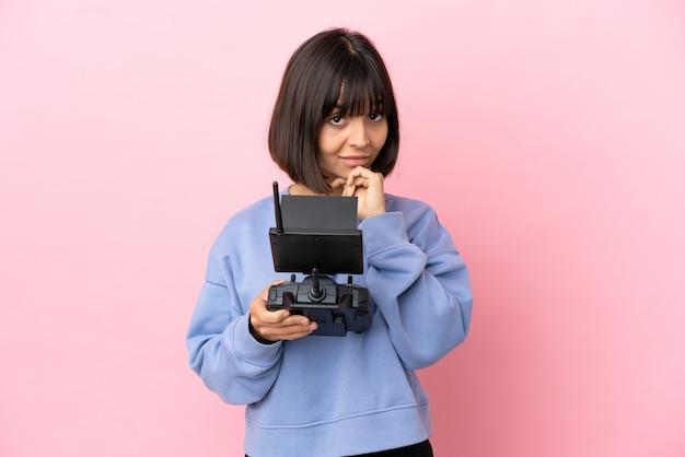 Молодая женщина смешанной расы, держащая пульт дистанционного управления дроном, изолированная на розовом фоне, думает