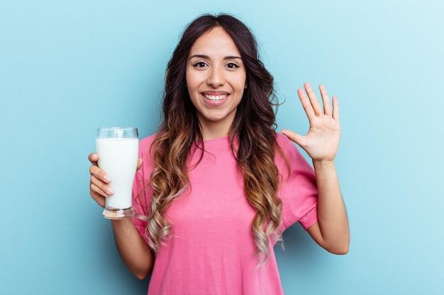 青い背景に分離されたミルクのガラスを保持している若い混血の女性は、指で5番を示して陽気に笑っています。