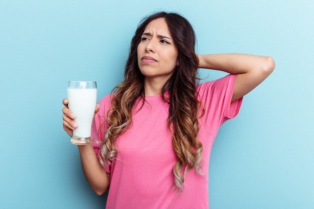 푸른 배경에 격리된 우유 한 잔을 들고 머리 뒤쪽을 만지고 생각하고 선택하는 젊은 혼혈 여성.
