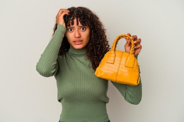 ショックを受けている白い背景で隔離のハンドバッグを持っている若い混血の女性、彼女は重要な会議を思い出しました。
