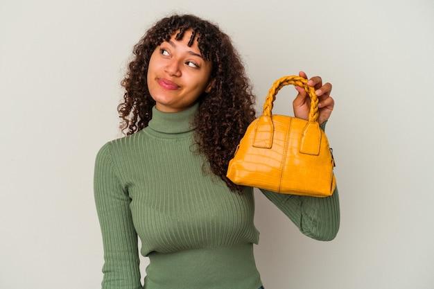目標と目的を達成することを夢見て白い背景で隔離のハンドバッグを保持している若い混血の女性