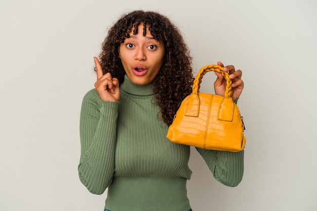 アイデア、インスピレーション コンセプトを持つ白い背景に分離されたハンドバッグを保持している若い混血女性。