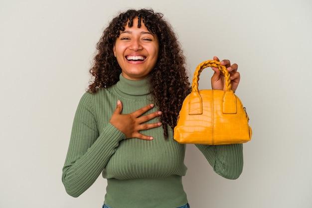 白い背景で隔離のハンドバッグを持っている若い混血の女性は、胸に手を置いて大声で笑います。
