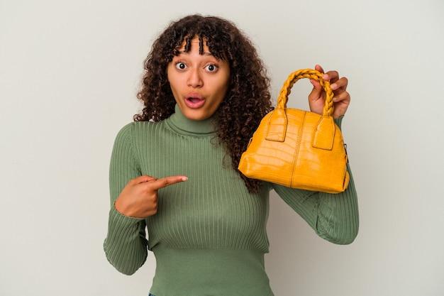側面を指している白い背景で隔離のハンドバッグを保持している若い混血の女性