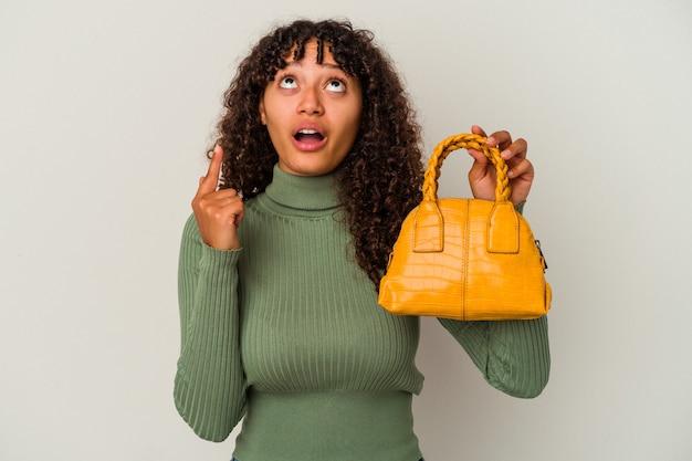口を開けて逆さまを指している白い背景で隔離のハンドバッグを保持している若い混血の女性。
