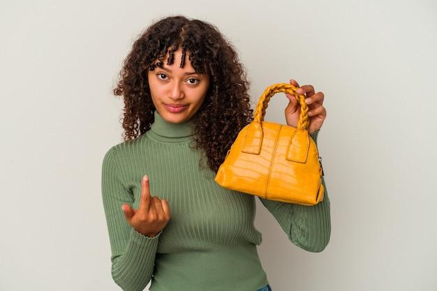 招待が近づくようにあなたに指で指している白い背景で隔離のハンドバッグを保持している若い混血の女性。
