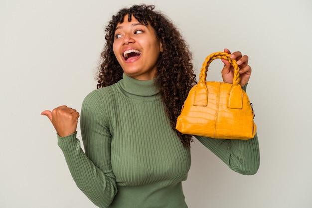 白い背景で隔離のハンドバッグを持っている若い混血の女性は、親指の指を離れて、笑って気楽にポイントします。