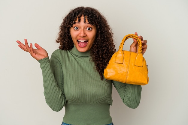 白い背景で隔離のハンドバッグを持っている若い混血の女性は、嬉しい驚きを受け取り、興奮し、手を上げます。