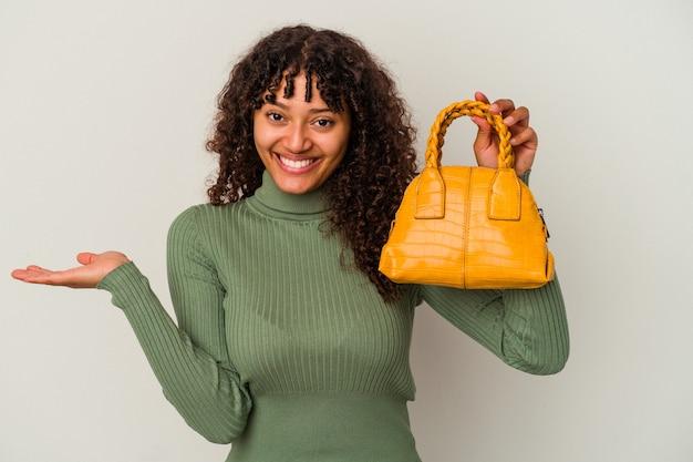 手のひらにコピースペースを示し、腰に別の手を保持している白い背景で隔離のハンドバッグを保持している若い混血の女性。