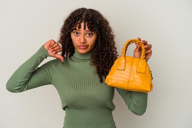嫌いなジェスチャーを示す白い背景で隔離のハンドバッグを持っている若い混血の女性は、親指を下に向けます。不一致の概念。