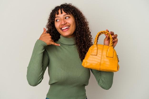 指で携帯電話の呼び出しジェスチャーを示す白い背景で隔離のハンドバッグを保持している若い混血の女性。