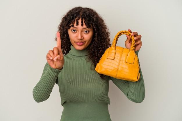 指でナンバーワンを示す白い背景で隔離のハンドバッグを保持している若い混血の女性。