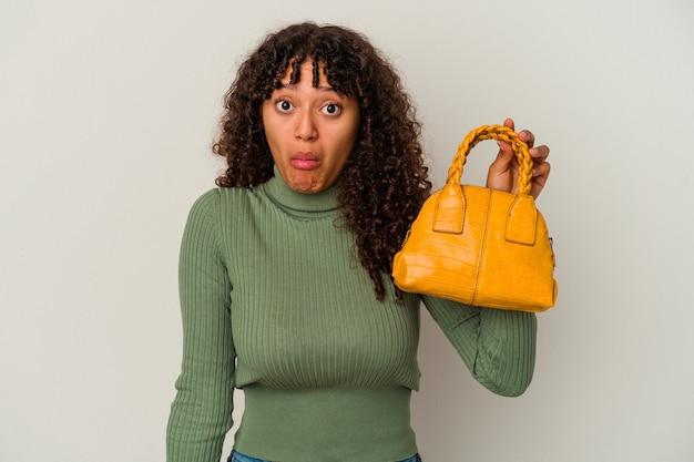 白い背景で隔離のハンドバッグを保持している若い混血の女性は、肩をすくめ、目を開けて混乱します。