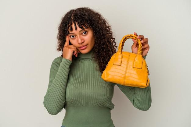 Молодая женщина смешанной расы, держащая сумочку, изолированную на белой стене, указывая висок пальцем, думая, сосредоточилась на задаче.