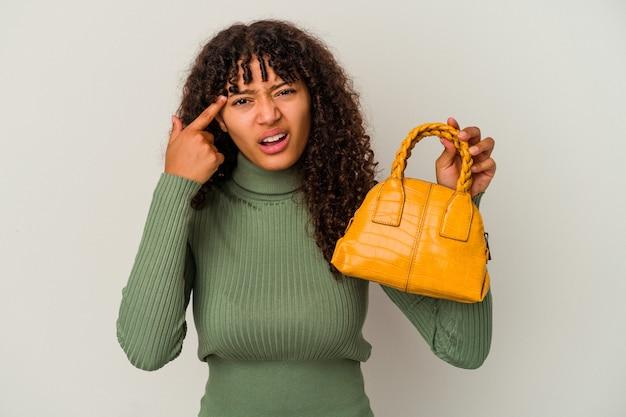 Молодая женщина смешанной расы, держащая сумочку, изолированную на белой стене, показывая жест разочарования с указательным пальцем.