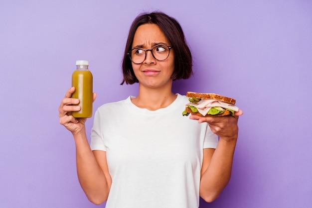 紫色の背景で隔離の健康的なスムージーとサンドイッチを保持している若い混血の女性