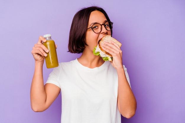 紫色の背景で隔離の健康的なスムージーとサンドイッチを保持している若い混血の女性 Premium写真