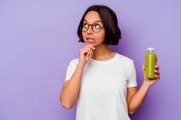 疑わしいと懐疑的な表現で横向きに見える紫色の背景に分離された健康的なスムージーを保持している若い混血の女性。