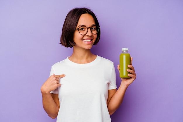 シャツのコピースペース、誇りと自信を持って手で指している紫色の背景の人に分離された健康的なスムージーを保持している若い混血の女性