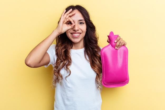 黄色の背景で隔離のホットバッグを保持している若い混血の女性は、目に大丈夫なジェスチャーを維持して興奮しています。