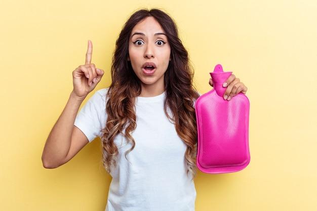 アイデア、インスピレーションのコンセプトを持つ黄色の背景に分離されたホットバッグを保持している若い混血の女性。
