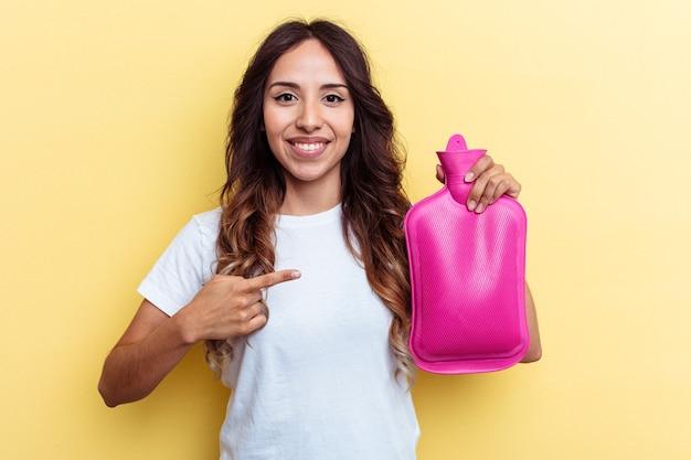 黄色の背景に分離されたホットバッグを持って笑顔で脇を指して、空白のスペースで何かを示している若い混血の女性。