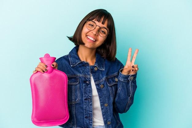 青い背景に分離された湯たんぽの水を持っている若い混血の女性は、指で平和のシンボルを喜んで気楽に示しています。