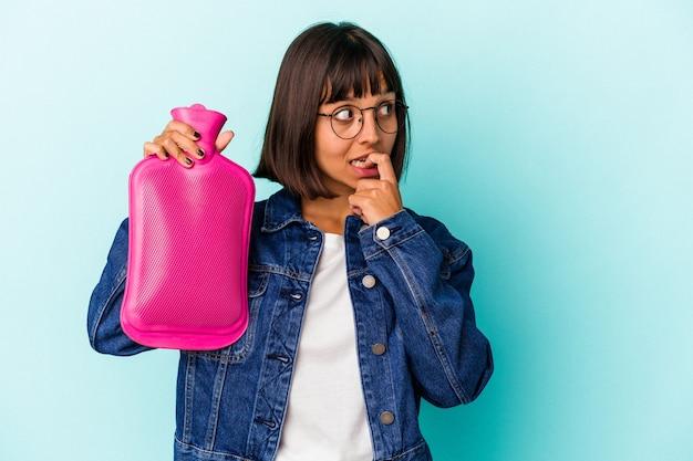 青い背景に分離された湯たんぽの水を保持している若い混血の女性は、コピースペースを見ている何かについて考えてリラックスしました。