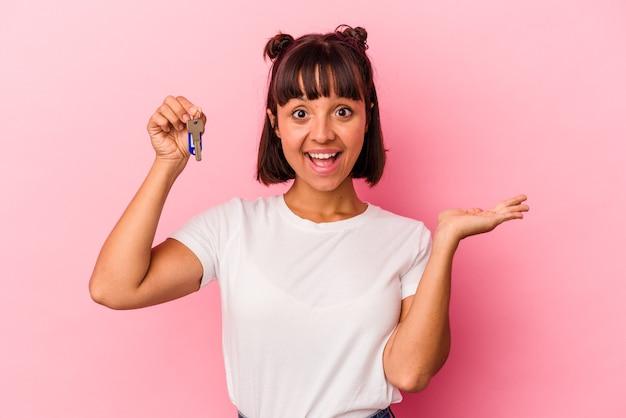 ピンクの背景で隔離のキーを保持し、手のひらにコピースペースを示し、腰に別の手を保持している若い混血の女性。