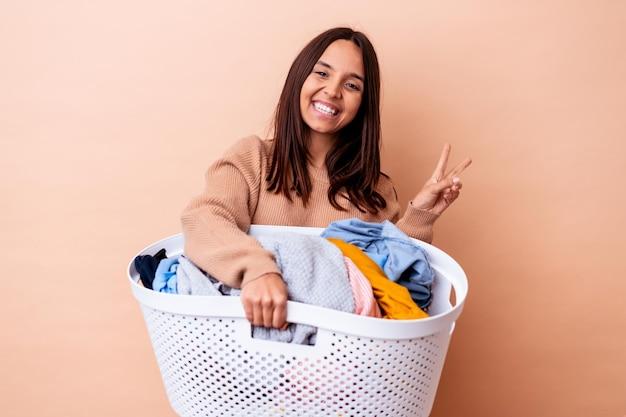 洗濯物を持っている若い混血の女性は、指で平和のシンボルを示して楽しくてのんきな孤立しました。