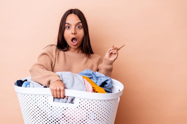 横を指して孤立した洗濯物を保持している若い混血の女性