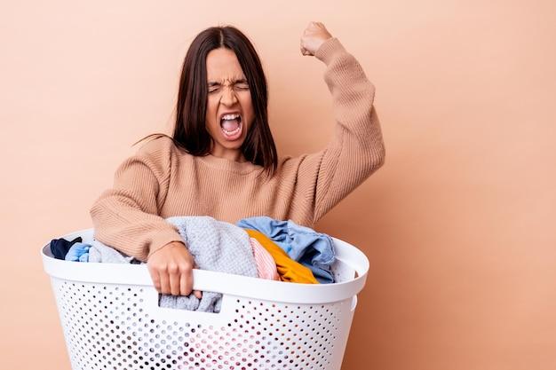 勝利の後に拳を上げて孤立した洗濯物を保持している若い混血の女性