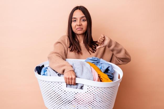 嫌いなジェスチャーを示す、孤立した洗濯物を保持している若い混血の女性、親指を下に
