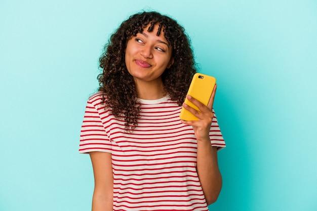목표와 목적을 달성하는 꿈을 파란색 배경에 고립 된 휴대 전화를 들고 젊은 혼혈 여자