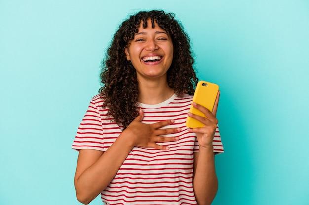 青の背景に携帯電話を持った若い混血の女性は、胸に手を当てながら大声で笑います。