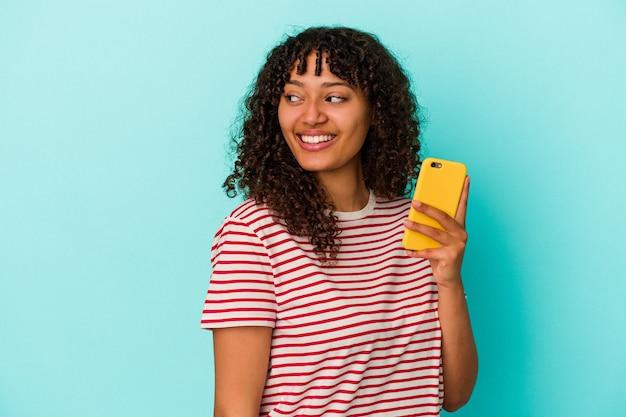 Молодая женщина смешанной расы, держащая мобильный телефон на синем фоне, смотрит в сторону, улыбаясь, веселая и приятная.