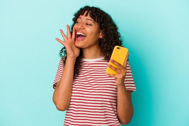 青の背景に分離された携帯電話を保持している若い混血の女性が叫び、開いた口の近くに手のひらを保持しています。