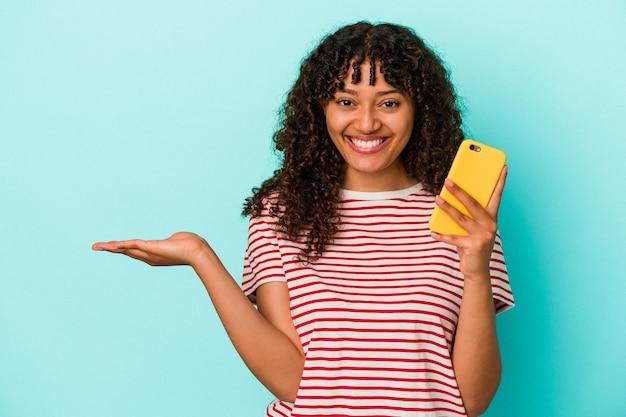 青の背景に携帯電話を持ち、手のひらにコピー スペースを表示し、腰に別の手を保持している若い混血の女性。