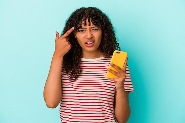 Молодая женщина смешанной расы, держащая мобильный телефон, изолирована на синем фоне, показывая жест разочарования указательным пальцем.
