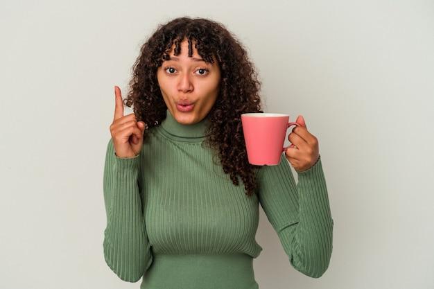 いくつかの素晴らしいアイデア、創造性の概念を持つ白い背景に分離されたマグカップを保持している若い混血女性。