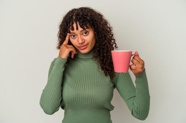 Молодая женщина смешанной расы, держащая кружку, изолированная на белом фоне, указывая висок пальцем, думая, сосредоточилась на задаче.