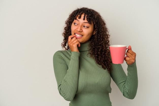 白い背景で隔離のマグカップを保持している若い混血の女性は、コピースペースを見ている何かについて考えてリラックスしました。