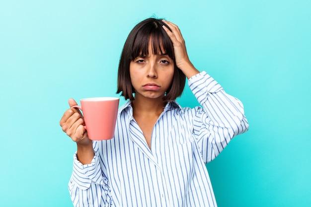 Молодая женщина смешанной расы, держащая розовую кружку, изолированную на синем фоне, потрясена, она вспомнила важную встречу.