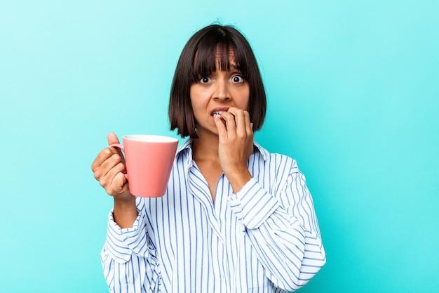 Молодая женщина смешанной расы, держащая розовую кружку, изолированную на синем фоне, кусая ногти, нервничает и очень тревожится.