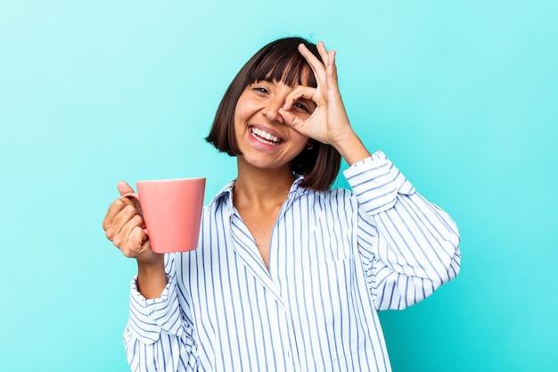 Молодая женщина смешанной расы, держащая розовую кружку, изолированную на синем фоне, взволнована, держа на глазах хорошо жест.