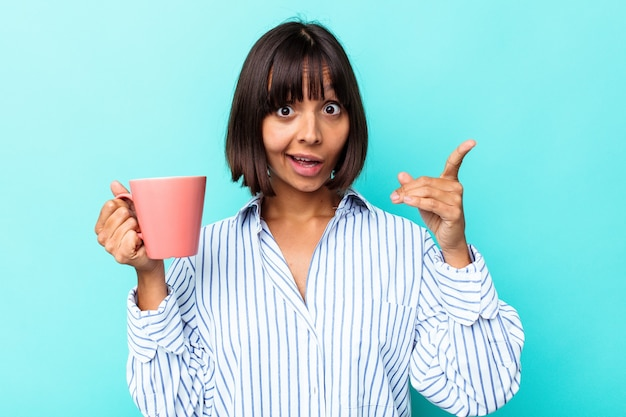 アイデア、インスピレーション コンセプトを持つ青の背景に分離されたピンクのマグカップを保持している若い混血女性。
