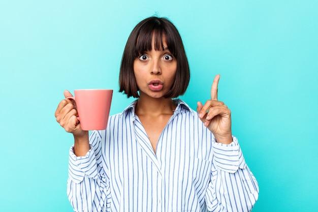 青の背景にピンクのマグカップを持った若い混血の女性が、素晴らしいアイデア、創造性のコンセプトを持っている。