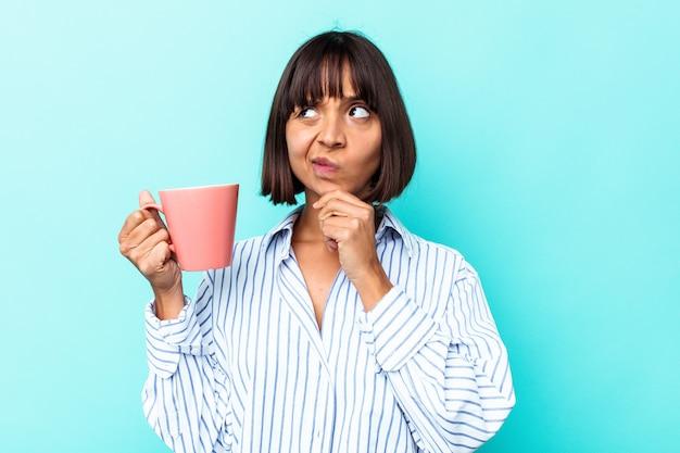 Молодая женщина смешанной расы, держащая розовую кружку, изолированную на синем фоне, смотрит в сторону с сомнительным и скептическим выражением лица.